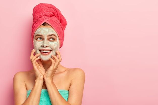 Mujer joven encantadora soñadora con máscara de arcilla, toca las mejillas, tiene expresión de alegría en la cara, dientes blancos, sueña con una piel perfecta, se ha envuelto una toalla en la cabeza, disfruta de tratamientos de belleza