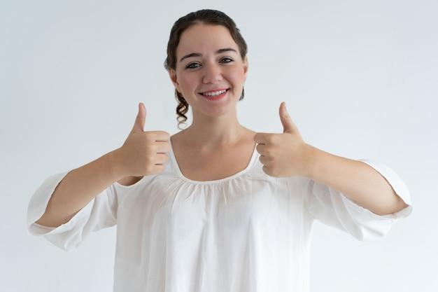 Mujer joven encantadora sonriente que muestra los pulgares para arriba
