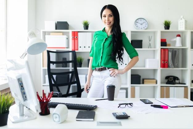Una mujer joven se encuentra cerca de un escritorio de oficina.