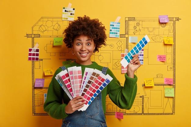 Mujer joven se encuentra junto al boceto de diseño de la casa listo para la renovación