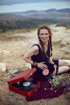 Mujer joven se encuentra en la naturaleza con un vestido negro junto a un viejo gramófono y escucha música
