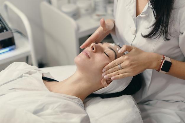 Mujer joven se encuentra con los ojos cerrados, cosmetóloga haciendo procedimiento