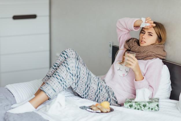 Mujer joven enferma en la cama con temperatura bebe té caliente y toca su cabeza
