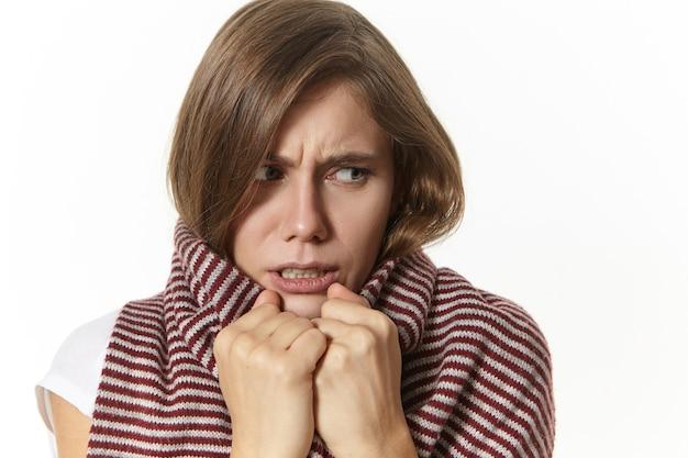 Mujer joven enferma frustrada envuelta en una bufanda a rayas que se congela debido a la alta temperatura, que sufre de resfriado o influenza, frunce el ceño, tiene una expresión facial dolorosa, posando aislada