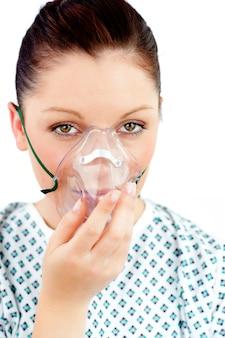 Mujer joven enferma con una máscara de oxígeno mirando a la cámara