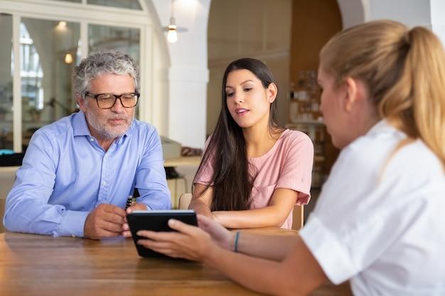 Mujer joven enfocada y hombre maduro reuniéndose con profesionales, viendo y discutiendo contenido en tableta