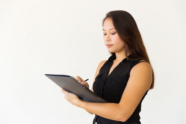 Mujer joven enfocada que escribe en carpeta