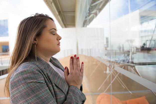 Mujer joven enfocada rezando con los ojos cerrados