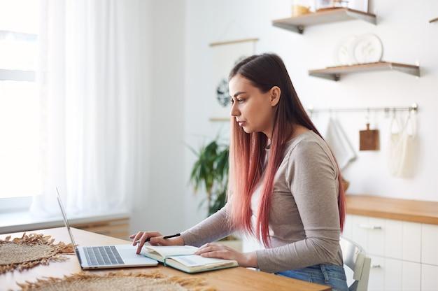 Mujer joven enfocada viendo un webinar, tomando notas en un cuaderno. aprendizaje a distancia en casa. trabajo remoto.