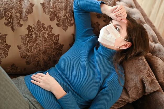 Mujer joven enmascarada con dolor de cabeza