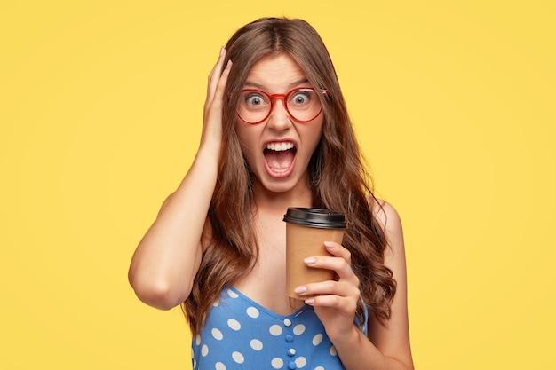 Mujer joven enojada con gafas posando contra la pared amarilla