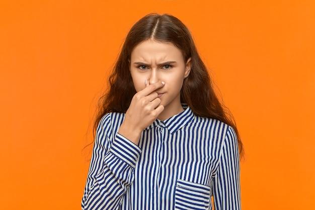 Mujer joven enojada insatisfecha con pelo ondulado suelto pellizcando su nariz