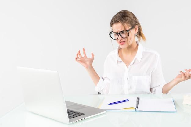 Mujer joven enojada que grita en el escritorio de oficina aislado sobre fondo