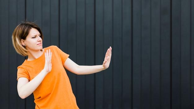 Mujer joven enojada que muestra gesto de la parada contra fondo negro