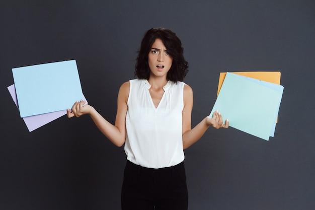 Mujer joven enojada que sostiene documentos en manos