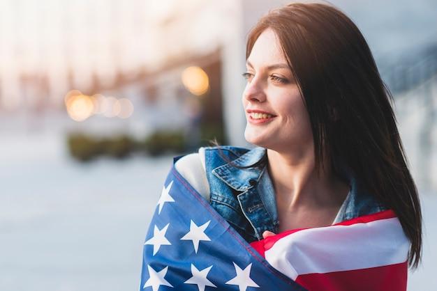 Mujer joven enrollando en la bandera estadounidense