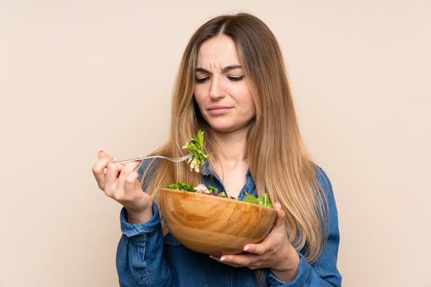 Mujer joven con ensalada sobre fondo aislado