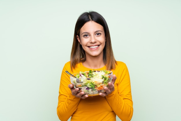 Mujer joven con ensalada sobre pared verde aislado