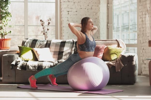 Mujer joven enseñando en casa cursos en línea de fitness, estilo de vida aeróbico y deportivo mientras está en cuarentena. ponerse activo mientras está aislado, bienestar, concepto de movimiento. ejercicios con fitball para la parte inferior del cuerpo.