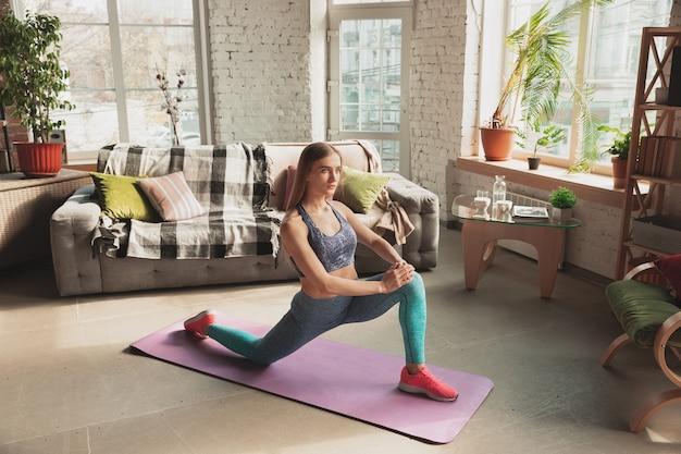 Mujer joven enseñando en casa cursos en línea de fitness, estilo de vida aeróbico y deportivo mientras está en cuarentena.