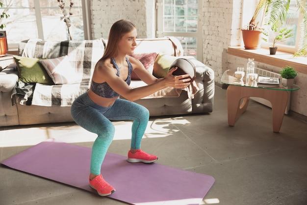 Mujer joven enseñando en casa cursos online de fitness