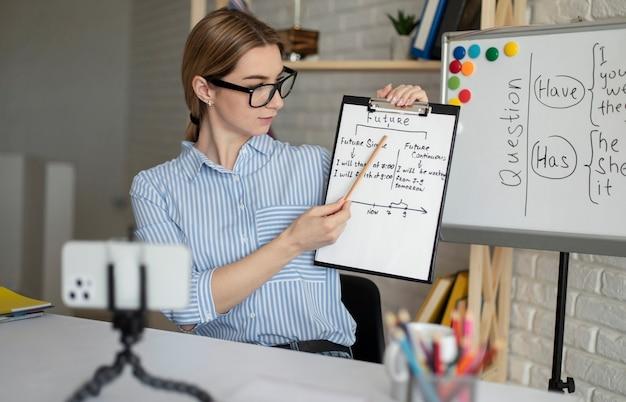 Mujer joven enseñando a los estudiantes una lección de inglés en línea
