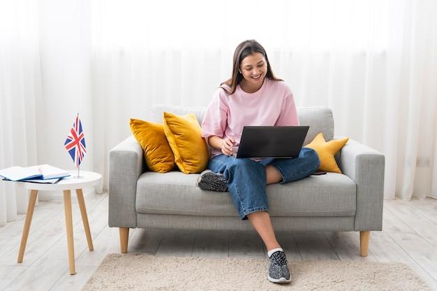 Mujer joven enseñando lecciones de inglés en línea en casa