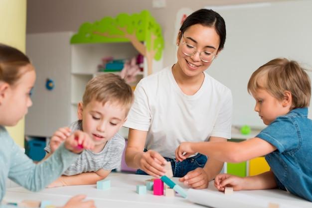 Mujer joven enseñando a los niños a jugar con juego colorido