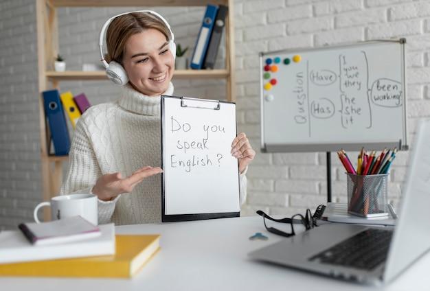 Mujer joven enseñando a los niños una lección de inglés en línea Foto Premium