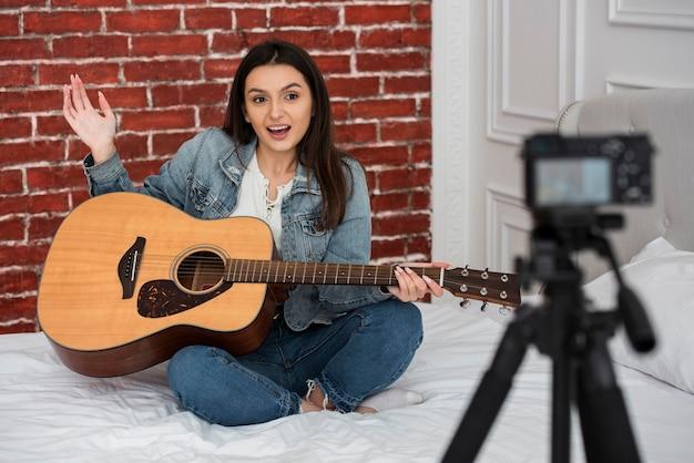 Mujer joven enseñando a tocar la guitarra