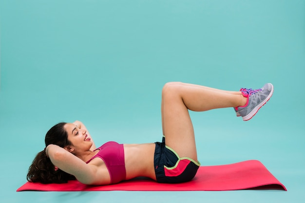 Mujer joven entrenando los abdominales