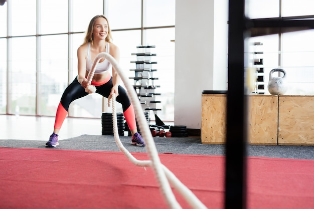 Mujer joven entrenando con cuerda de batalla en cross fit gym