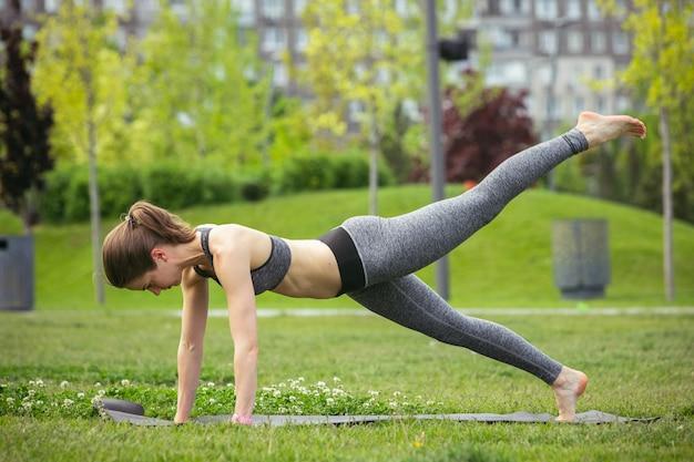 Mujer joven entrenando en parque público en verano