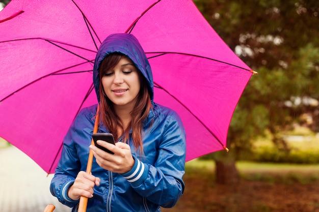 Mujer joven enviando mensajes de texto en el teléfono móvil bajo la lluvia
