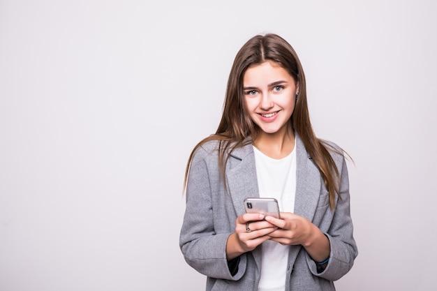 Mujer joven enviando un sms por teléfono celular, aislado sobre fondo blanco.