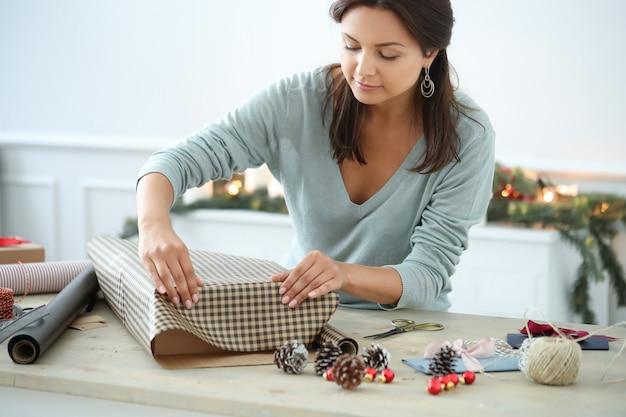 Mujer joven envolviendo regalos de navidad