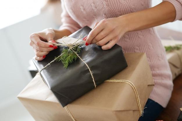 Mujer joven envolviendo regalos