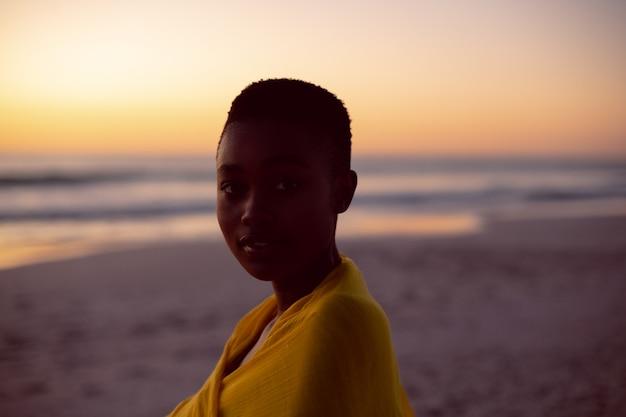 Mujer joven envuelta en un pañuelo amarillo en la playa