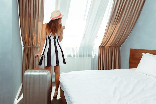 Mujer joven con equipaje en la habitación del hotel