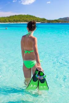 Mujer joven con equipo de snorkel en playa tropical