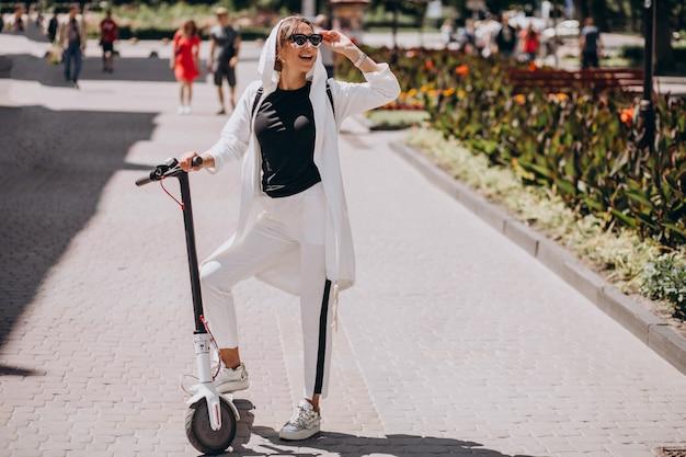 Mujer joven, equitación, patineta, en la calle