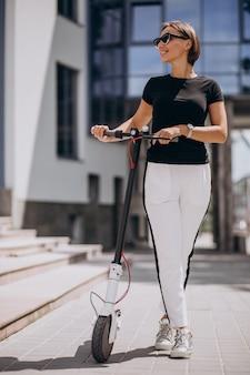 Mujer joven, equitación, scotter, por, el, rascacielos