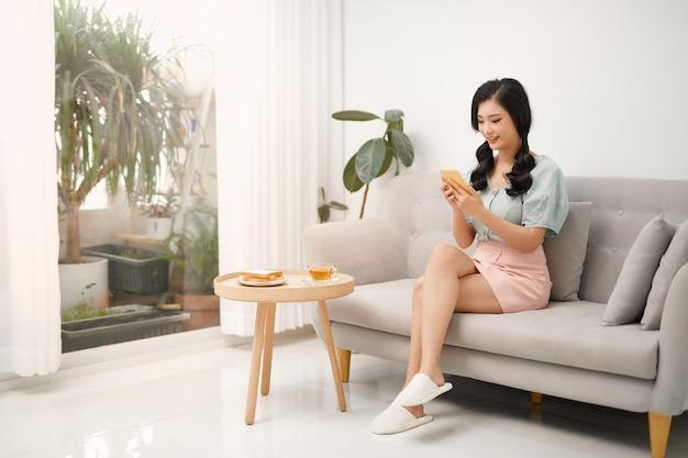 Mujer joven es chat en un teléfono inteligente en un sofá.