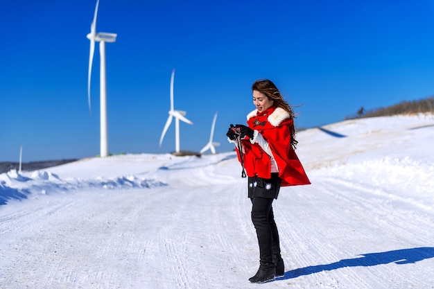 La mujer joven es una felicidad con la cámara en invierno del cielo y la carretera de invierno con nieve y vestido rojo