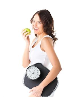 Mujer joven con escala debajo de su brazo y manzana