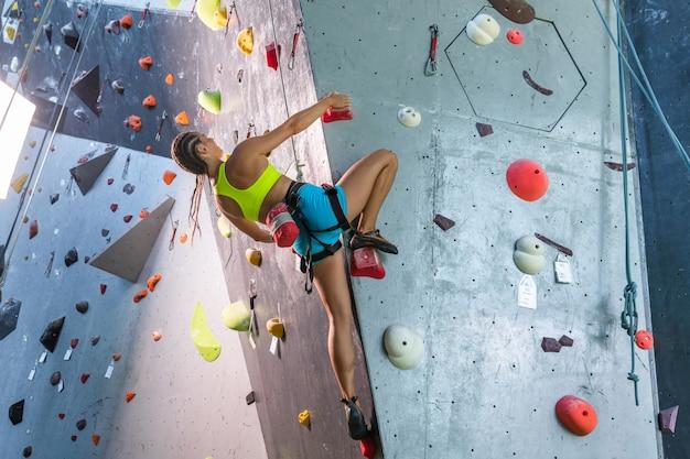 Mujer joven escalador está escalando en el interior escalada gimnasio