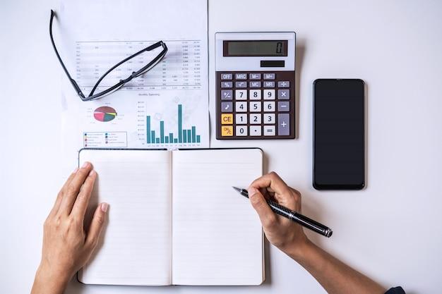Mujer joven escribiendo y calculando gastos en casa, vista superior