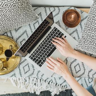Mujer joven escribiendo en la computadora portátil en la cama. encabezado de héroe de estilo de vida con vista desde arriba