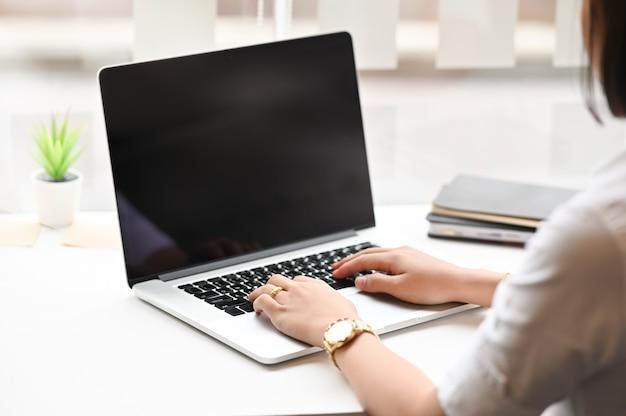 Mujer joven escribiendo computadora portátil en la mesa