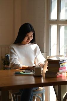 Mujer joven escribiendo en la computadora portátil y la pila de libros.